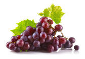 Fotografie Bunch of ripe red grapes with leaves isolated on white