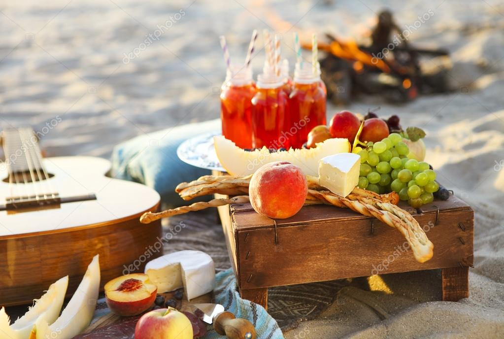 Picnic on the beach at sunset with fruits and juices
