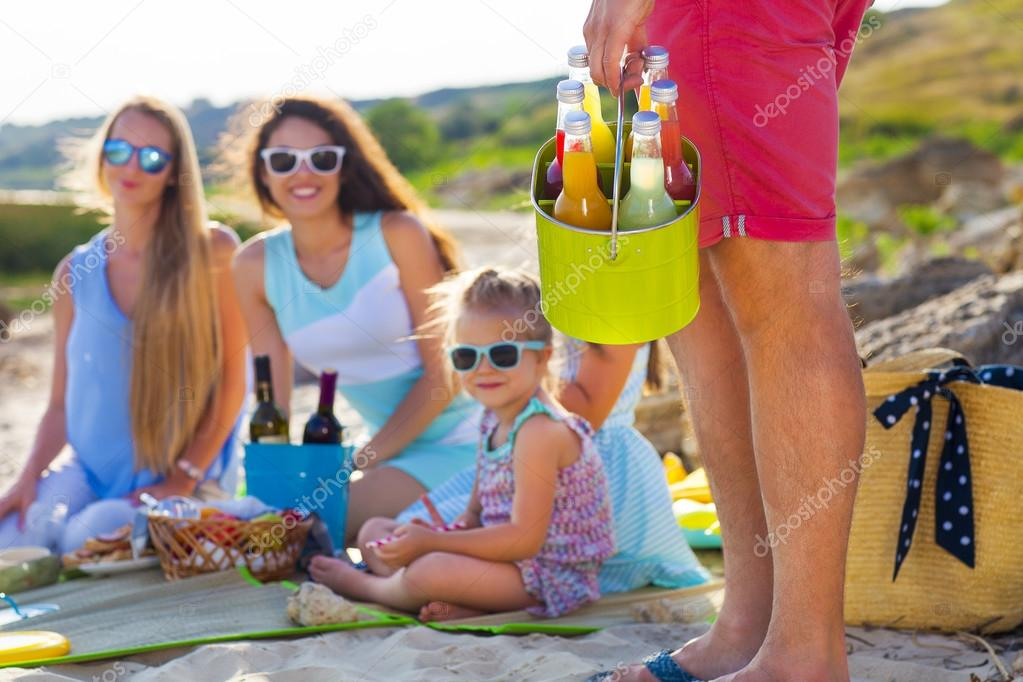Friends sitting on the sand at the beach at the summer picnic. O