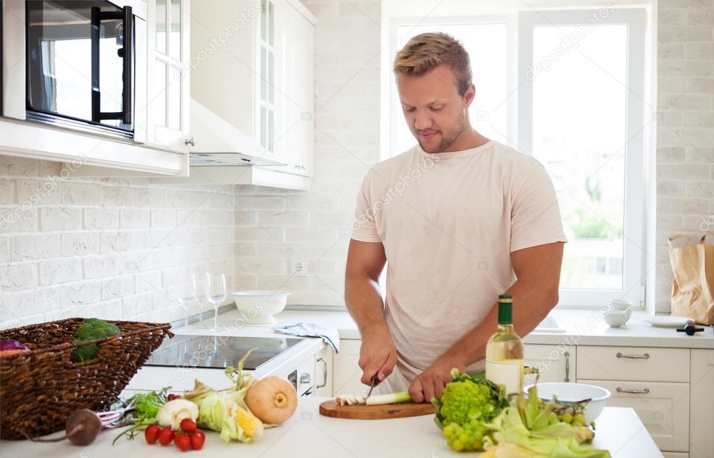 Gut aussehender mann kochen zuhause vorbereiten salat in for Cocinar huevos 7 days to die
