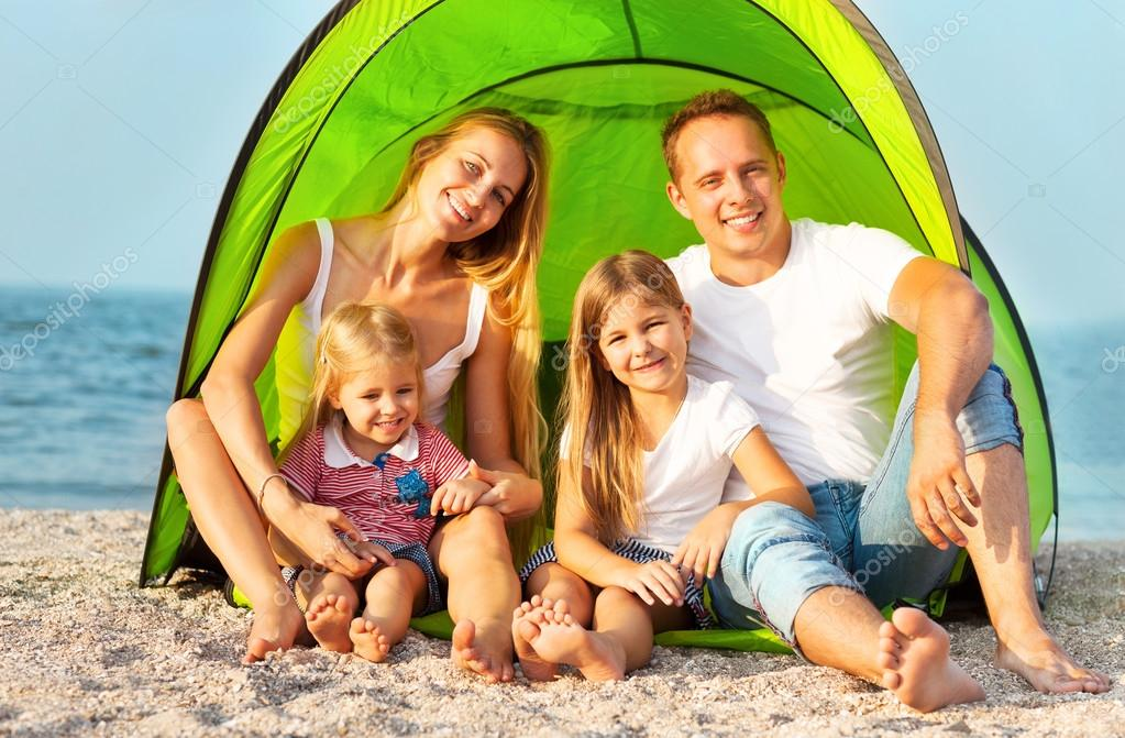 Happy young family camping on the beach