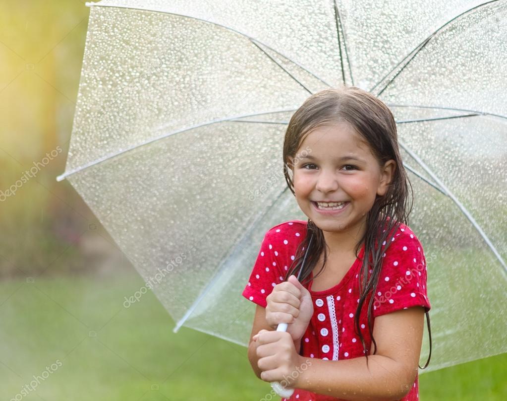 Child with wearing polka dots dress under umbrella