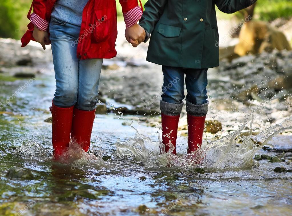 Child wearing rain boots jumping. Close up