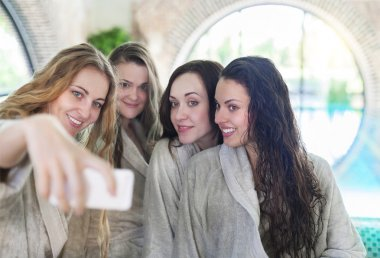 Young women relaxing in the spa resort doing selfy wearing towel