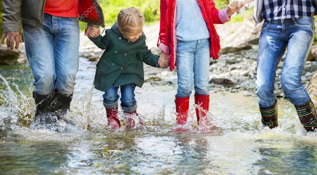 Happy family wearing rain boots jumping into a mountain river