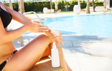 Woman applying sun cream. Sexy blond woman in bikini relaxing be