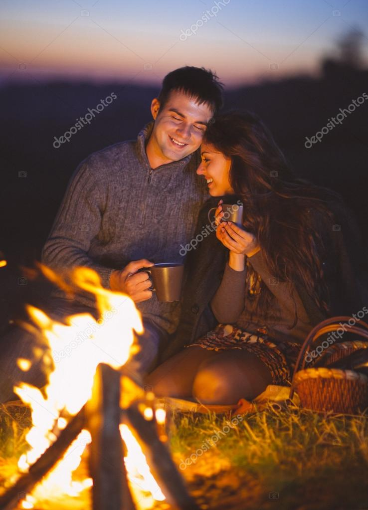 Portrait of the happy couple sitting by fire on autumn beach