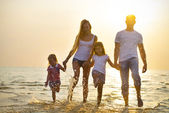 Fotografie Happy young family having fun running on beach at sunset. Family