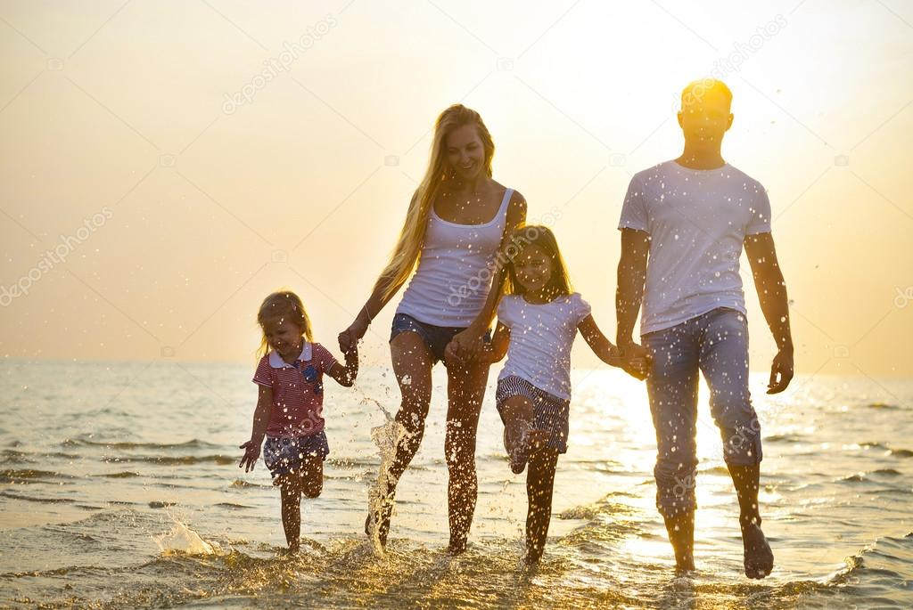 Happy young family having fun running on beach at sunset. Family