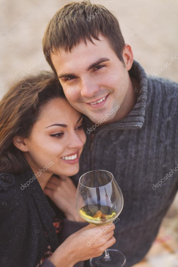 Young happy couple enjoying picnic with white wine on the beach