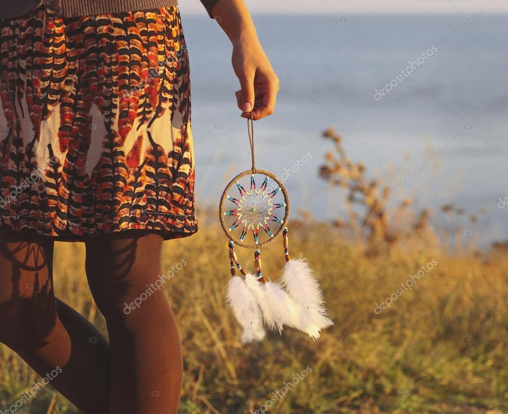 Brunette woman with long hair holding dream catcher
