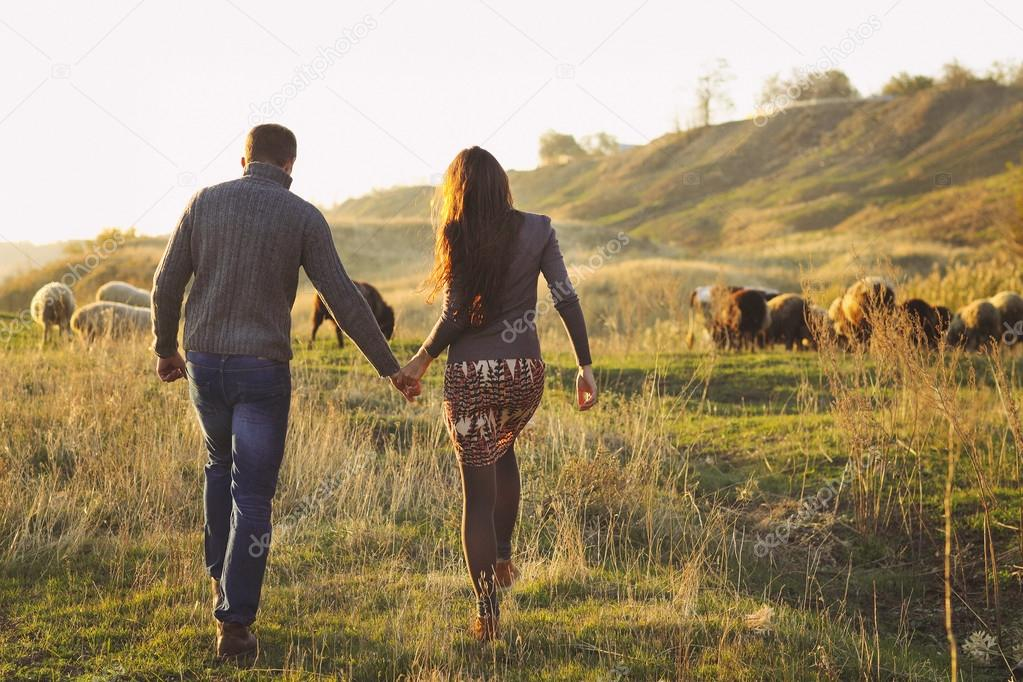 Couple holding hand in hand romantic walk on the autumnal meadow