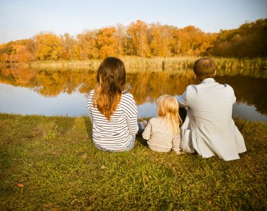 Happy family - mother, father and daughters relaxing at autumn c