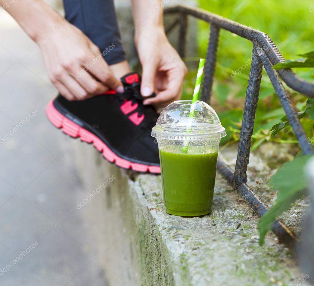 5b50dc83d549 Zöld méregtelenítő smoothie kupa és a nő befűzési futócipő előtt w — Stock  Fotó