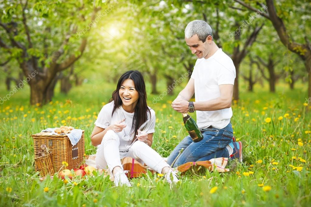 Happy smiling couple drinking champagne at picnic