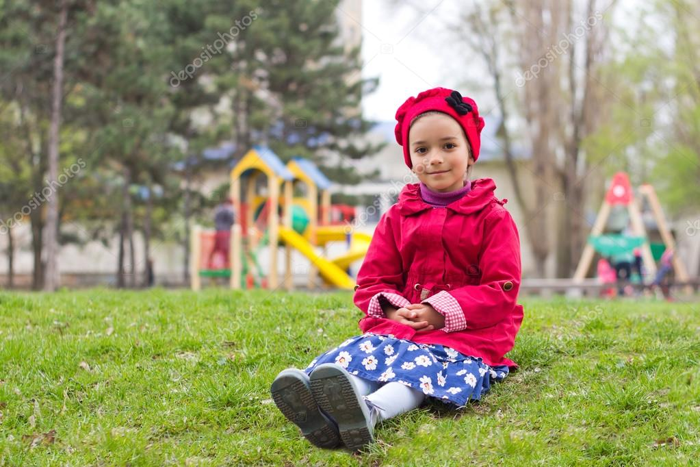 8245cac1c25 Μικρό κορίτσι συνεδρίαση για την πράσινη χλόη την παιδική χαρά στην ...