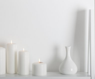 white candles burning on a white shelf