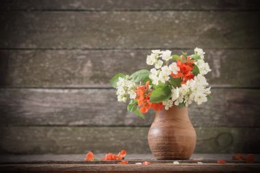 Flowers in jug on wooden background stock vector