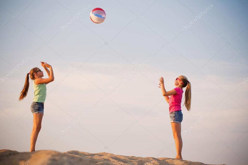 girls playing on beach with ball