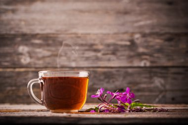 cup of tea with willow-herb on wooden background