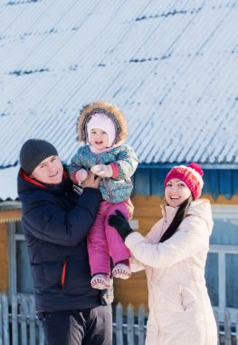 Happy family in warm clothes standing of his house in winter