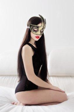 girl in mask kneeling on white bed