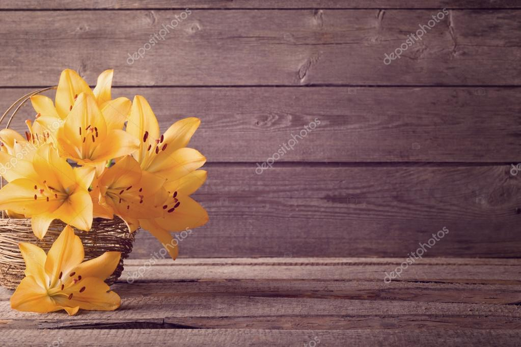 orange lily in basket on wooden background