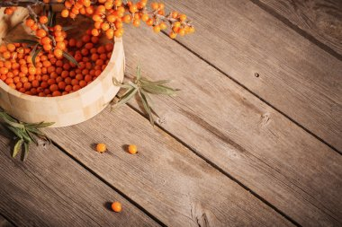 Sea buckthorn berries on a wooden background