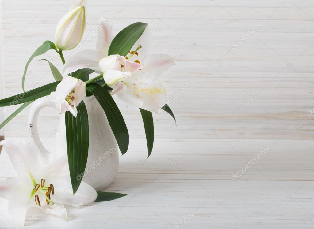 lily in jug on white wooden background
