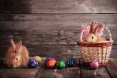 Fotografie rabbits with Easter eggs on wooden background