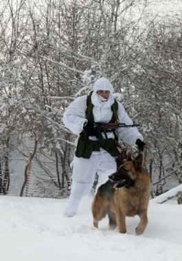 Saratov, Russia December 12, 2007: A border guard with a dog in a snowy forest border guards on the teachings of the border department of the FSB of Russia in Saratov and Samara regions.