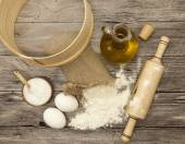 Wheat flour in a canvas bag,sieve, the olive oil in a glass carafe, a large salt shaker wood, raw eggs, a wooden rolling pin: set for making homemade bread dough on a beautiful dark wooden background