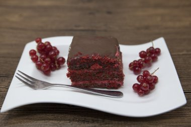 Red Velvet, fresh delicious diet cake with red currant at Dukan Diet on a porcelain plate with a spoon on a wooden background