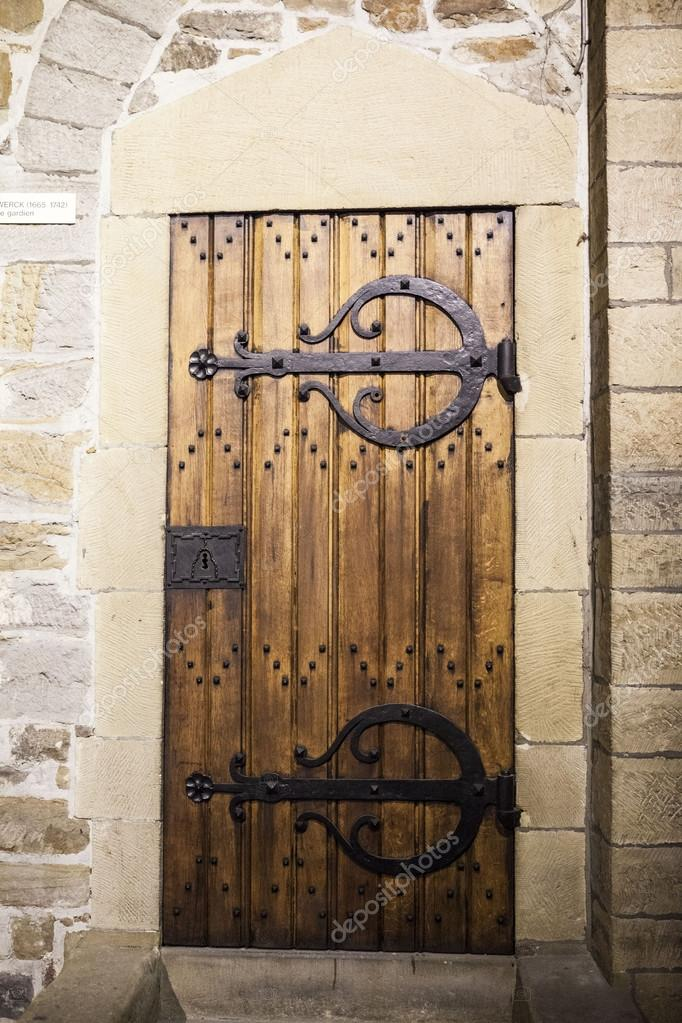 A large wooden door closed an old fortress in the stone wall of ...