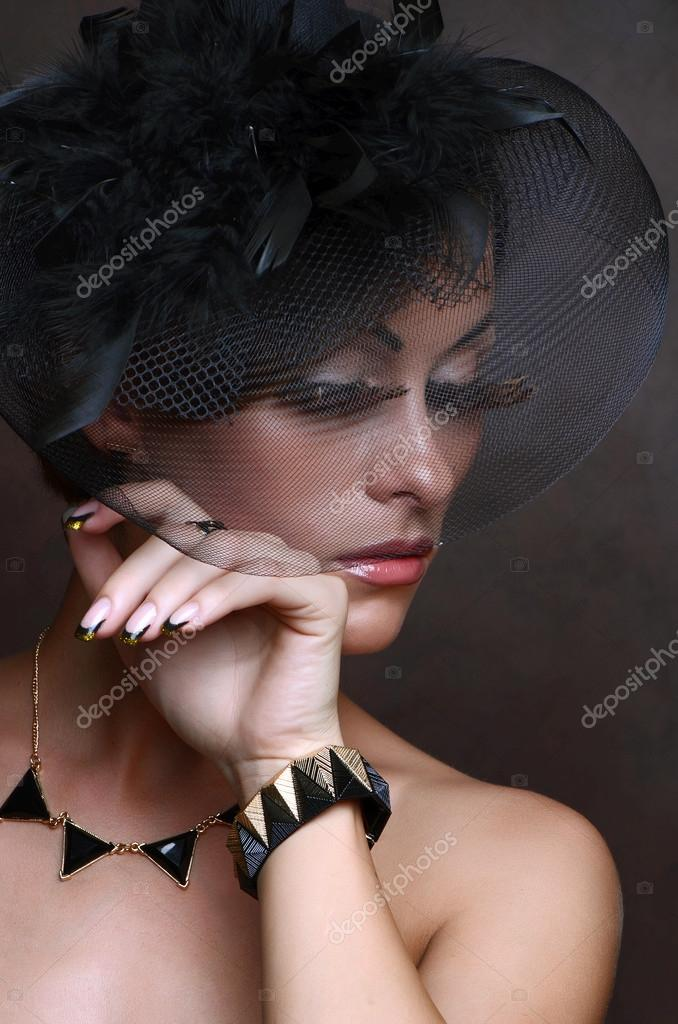 Portrait of retro-stylized woman in black hat with veil on gray background  — Photo by ... a8192f56eee3