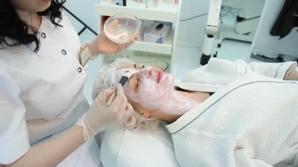 Ruce kosmetolog naneste krém na půl
