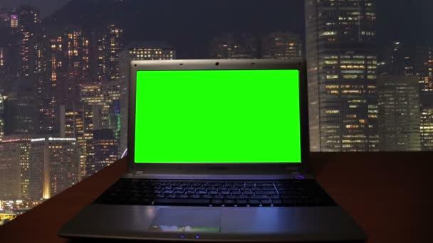Notebook s zelené v temné místnosti