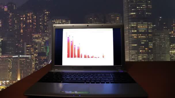 Přenosný počítač s grafy v temné místnosti na pozadí města v noci.