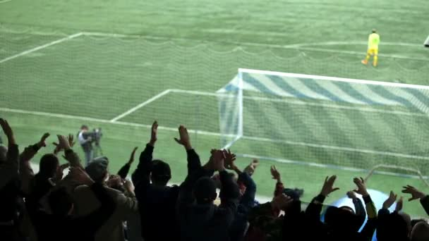 A rajongók a háttérben, mint egy futballpálya sziluettek.