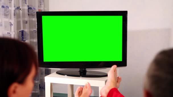 Muž a žena, dívat se na televizi. Zelená obrazovka