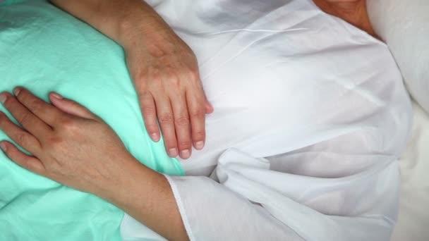 Detail ženského těla v nemocniční posteli