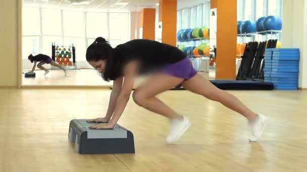 krásná žena na palubě krok, během cvičení