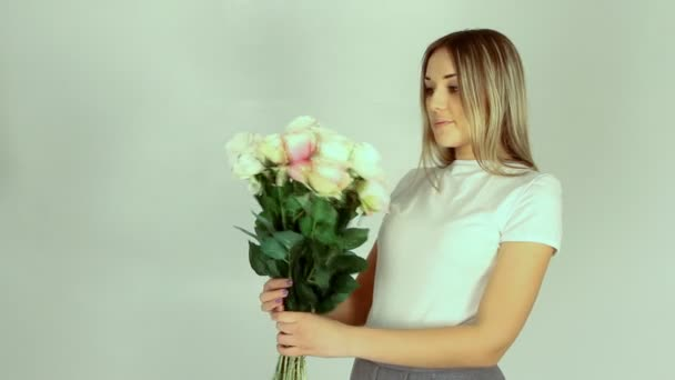 Young romantic woman with bouquet of many roses