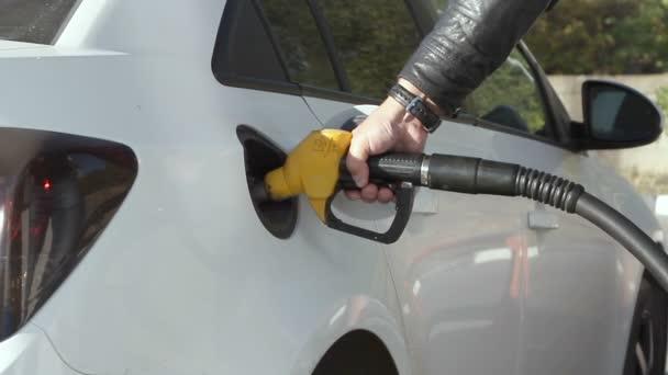 man pumpt Benzin Kraftstoff im Auto an Tankstelle.