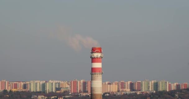 Kouřící elektrárna komín s domy v pozadí