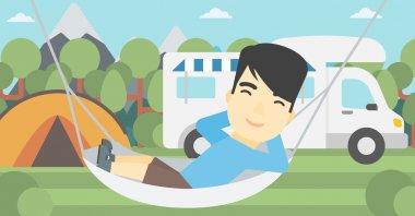 Man lying in hammock in front of motor home.