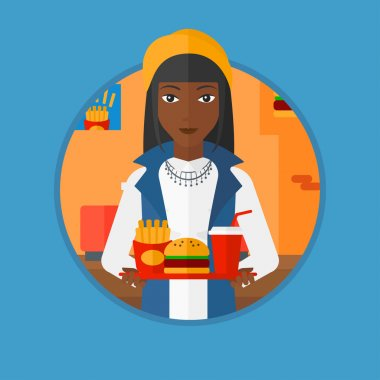 Woman with tray full of fast food.