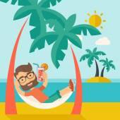 Mladý muž na pláži th uvolňující a pít koktejl