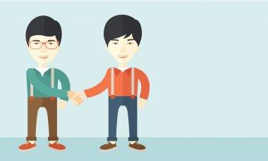 Two asian guys happily handshaking.