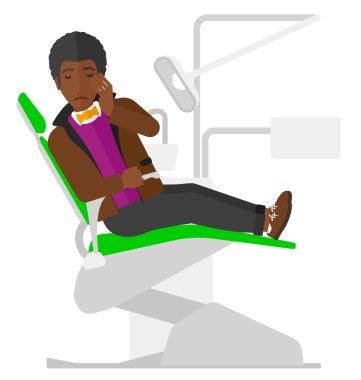 Man suffering in dental chair.